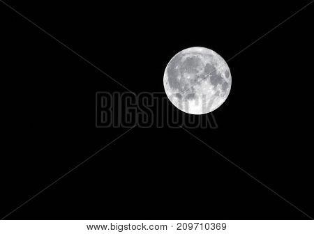 silver full harvest moon in a dark black sky
