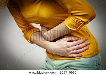 Health care concept. Bellyache indigestion or menstruation. Young female suffering from strong stomach ache abdominal pain on gray