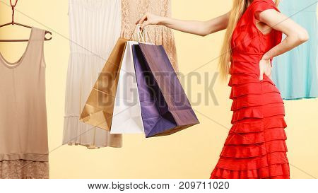 Woman in clothes shop store holding shopping bags picking summer perfect outfit dress hanging on clothing hangers