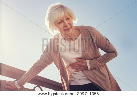 Acute pain. Petite elderly woman leaning on a concrete block with one hand and pressing her hand to the subcostal area while suffering from pain