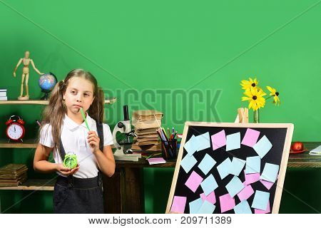 Childhood And Study Time Concept. Girl Holds Green Clock