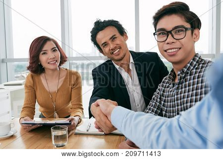 Group of Vietnamese young people happy to meet new colleague
