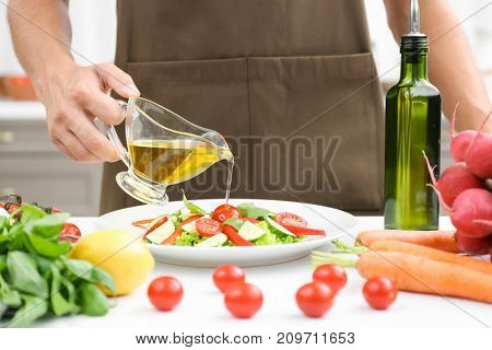 Man pouring cooking oil onto vegetable salad in kitchen