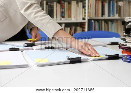 Woman working with documents at table in archive