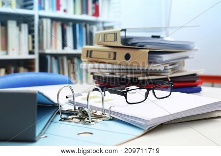 Documents and glasses on table in archive