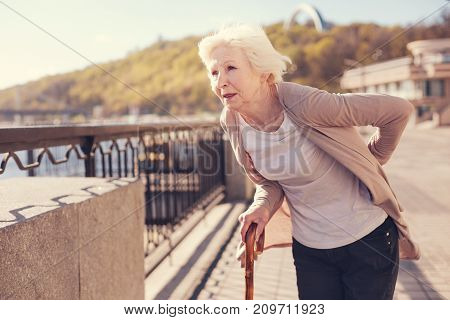 Sharp pain. White-haired senior lady standing on the bridge and touching her sore lower back while looking into the distance