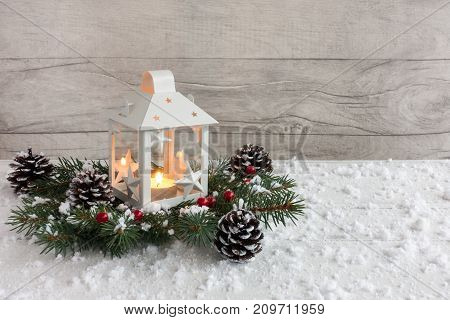 White Christmas lantern with lit candle on fir tree twigs decorated with holly berries pine cones and snowflakes.
