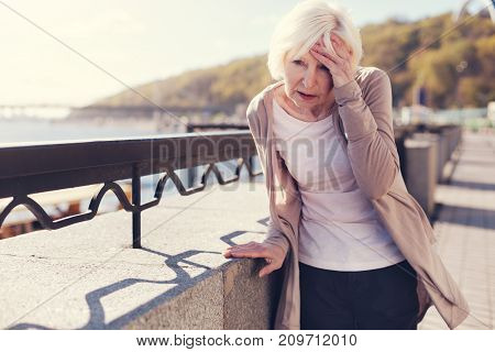 Splitting headache. White-haired petite senior lady leaning on a concrete block of a bridge and pressing one hand against her forehead while suffering from migraine