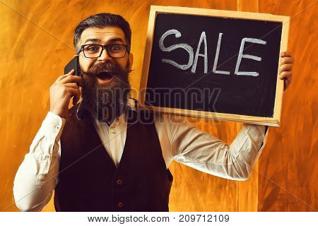 Bearded Man, Brutal Caucasian Hipster With Smartphone Holding Sale Inscription