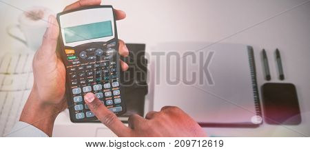 Cropped hands of businessman using calculator  against high angle shot of documents with diary and technologies