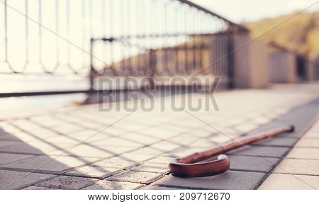 Lost on bridge. The focus being on a wooden cane lying on a paved sidewalk of a bridge, having been lost by its owner