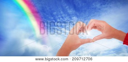 Woman making heart shape with hands against tranquil scene of overcast against sky