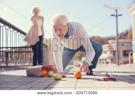 Unfortunate accident. Pleasant elderly man gathering fruit scattered on the ground, having fallen down, while a woman rushing towards him to help