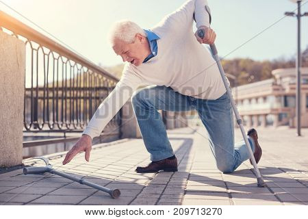 Difficult attempts. White-haired elderly man leaning on his crutch and trying to reach for another one while trying to get up after having fallen down