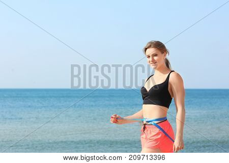 Young sporty woman measuring waist on sea beach