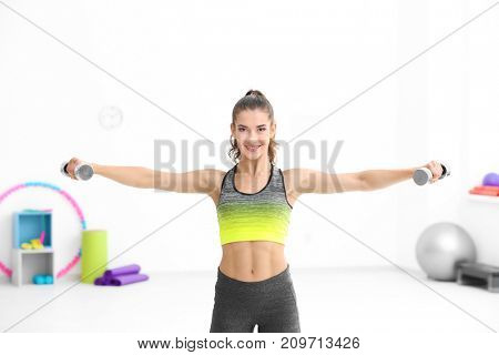 Young sporty woman training with dumbbells in gym