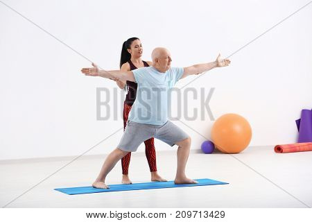Mature man with personal yoga instructor indoors