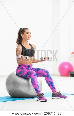 Young sporty woman training with dumbbells on fitness ball in gym