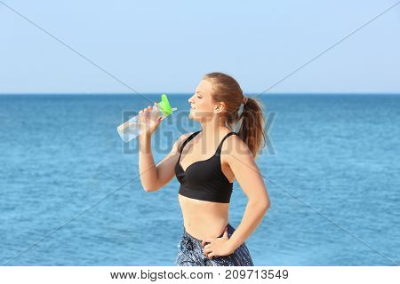 Young sporty woman with bottle of water on sea beach