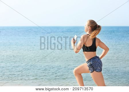 Young sporty woman running on sea beach