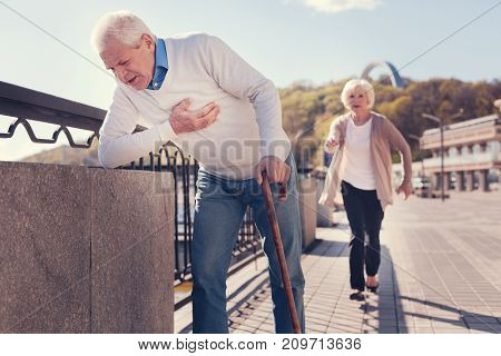 Coming to rescue. Petite senior woman running to a white-haired elderly man leaning on a concrete block of the bridge because of weakness caused by a heart attack