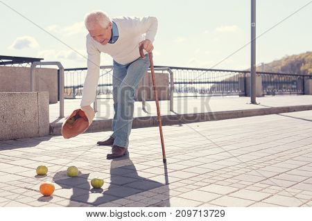 Disappointing accident. White-haired elderly man with a cane dropping a bag of fruit and scattering apples and oranges on the ground