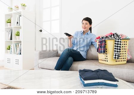 Smiling Woman Using Television Remote Control