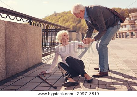 True gentleman. Courteous senior man holding a hand of an elderly woman and trying to help her get up from the ground