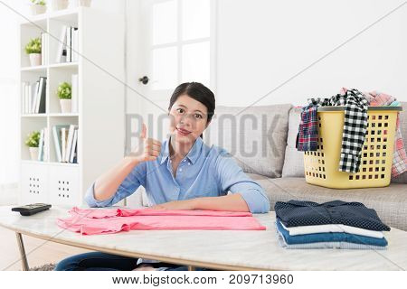 Happy Attractive Housewife Folding Family Clothing