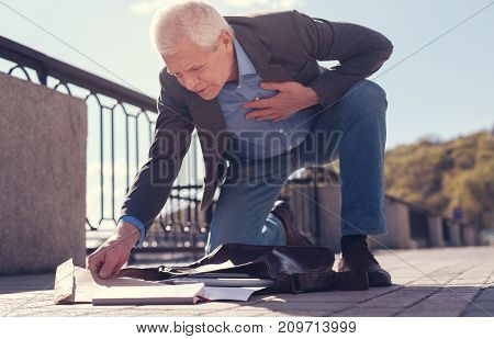 Feeling poorly. Handsome elderly man gathering his scattered belongings to a leather bag while touching his sore heart and feeling unwell