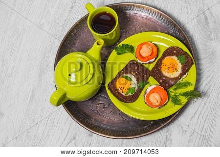 Breakfast -  toast with processed cheese tomato, fried eggs , fried eggs, teapot and cup of tea on a gray wood background. Flat lay. Top view.