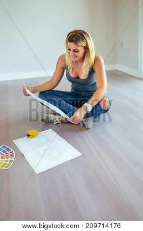 Girl looking house plans sitting on the floor