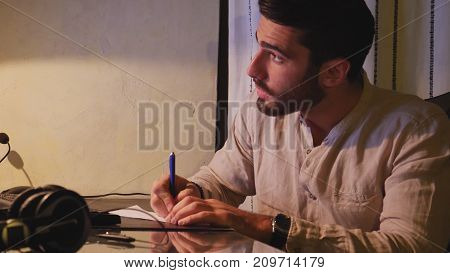 Stylish young man sitting at his desk at home at night, working on paperwork taking notes and making amendments in front of computer