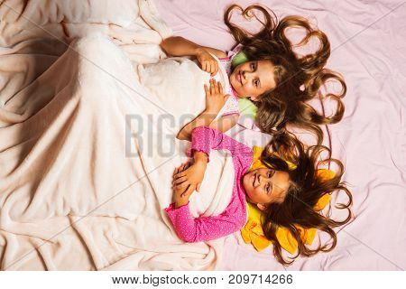 Schoolgirls Have Pajama Party. Kids In Pink Pajamas Under Blanket