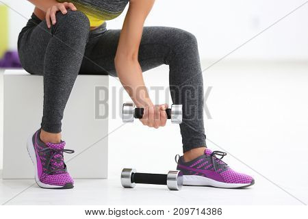 Young sporty woman training with dumbbell in gym