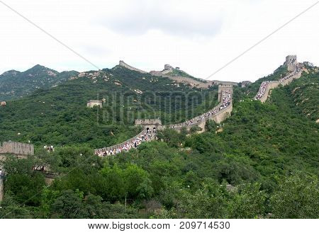 View of crowded Great Wall of China with green surrounding nature