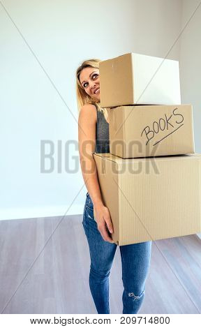Smiling blond woman carrying three moving boxes