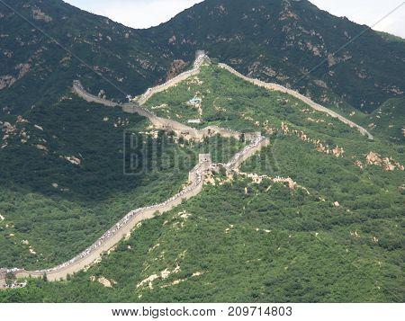 Blurred view of Great Wall of China with green surrounding nature for background