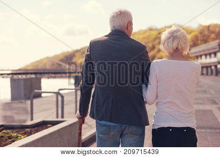 Romantic mood. Loving senior couple going arm in arm while having a walk along embankment