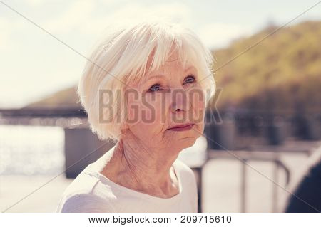 Full of melancholia. The close up of a beautiful white-haired elderly woman looking at the distance with a wistful look while pondering something upsetting