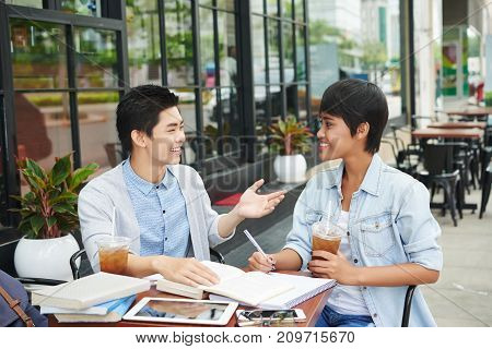 Cheerful Asian young people drinking iced tea and discussing homework in cafe