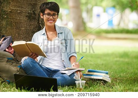 Pretty Indonesian female student in glasses sitting on campus and reading a book