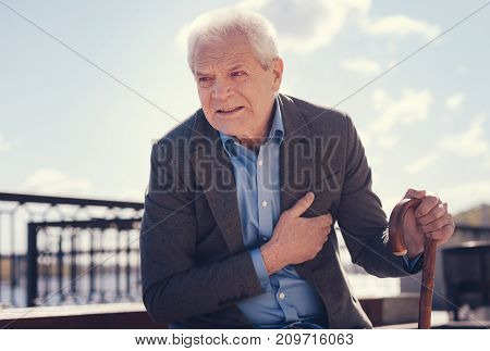 Wincing in pain. White-haired elderly man holding a cane and touching his chest because of suffering from angina