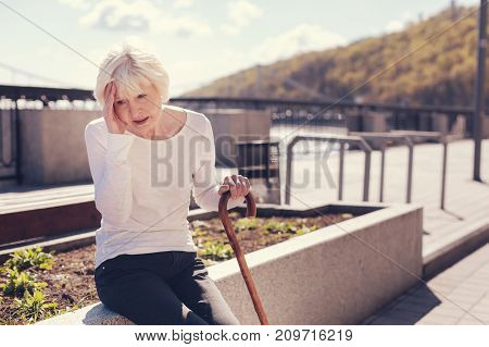 Throbbing pain. Slender senior woman sitting on a concrete edge of a flower bed, leaning on a cane and pressing her hand to a sore head