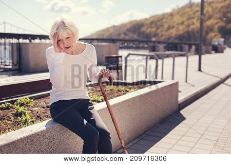 Excruciating pain. Petite senior woman sitting with a cane on a concrete edge of a flower bed and suffering from a splitting headache while pressing her hand to the temple