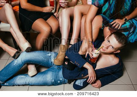 Sexy young male in women company. Submissive man on floor, sexual mood with drinks. Unrecognizable females, seduction and pickup concept