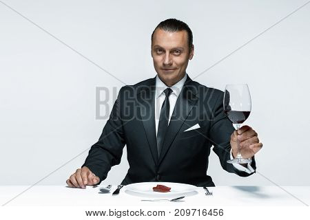 Portrait of a young man in image of maniak with knife, fork and and a piece of raw meat on a plate. Man in suit. The image in the style of Halloween