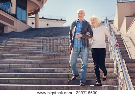 Together forever. Pleasant senior couple going down the stairs arm in arm while the woman holding onto handrail