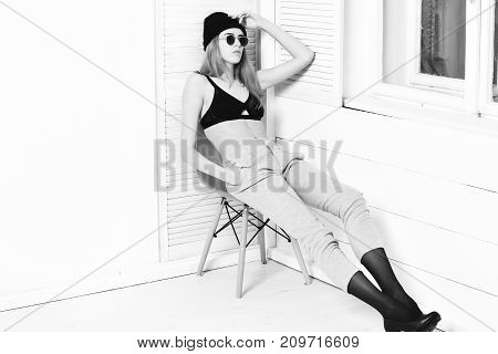 Pretty Sexy Woman In Sunglasses, Bra, Hat On Orange Chair