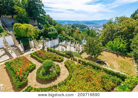 Spectacular aerial view of flowering garden in front of Sanctuary of Bom Jesus do Monte and the monumental baroque staircase. Cityscape of Braga from top of mountain. Tenoes, Braga, north of Portugal.